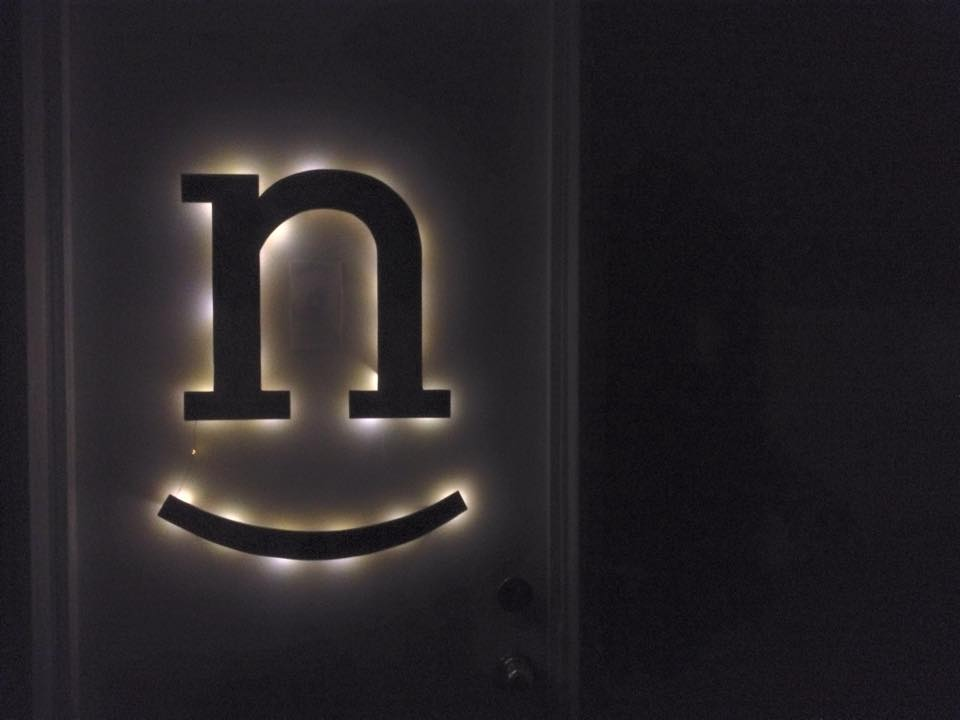 Illuminated wooden Nicer mark hanging in the studio after dark.