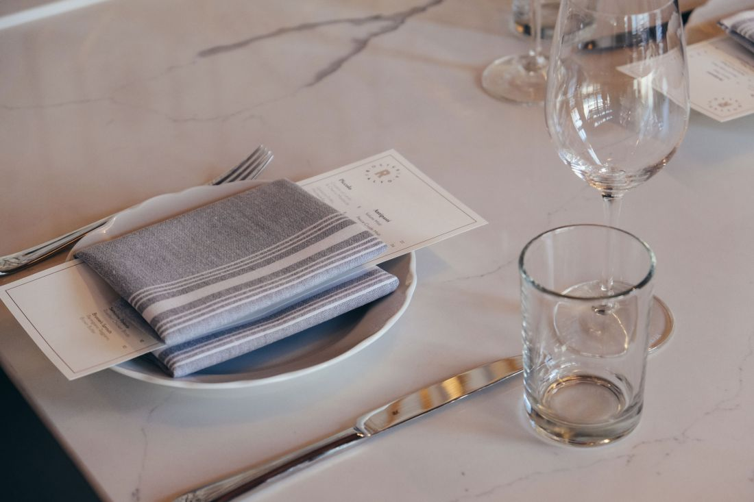 Place setting on a marble table top with Osteria Rialto menu