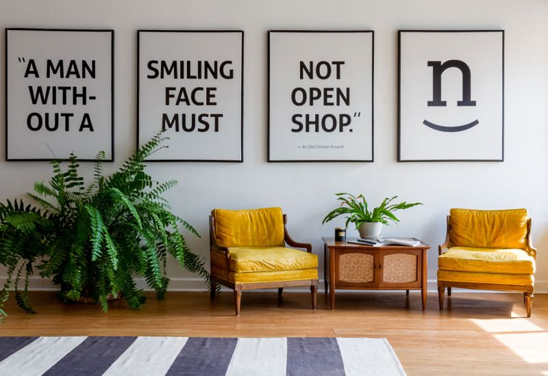 Beautiful space with a large fern, two yellow upholstered lounge chairs, a nicely decorated coffee table and four-panels of large wall art reading: A man without a smiling face must not open shop.